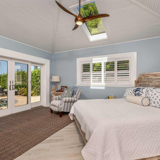 Inspiration for a mid-sized coastal master ceramic tile and vaulted ceiling bedroom remodel in Tampa with blue walls