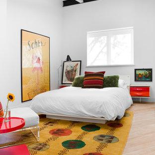 Modelo de habitación de invitados industrial, de tamaño medio, con paredes blancas, suelo de madera clara y suelo marrón