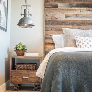 Modelo de dormitorio principal, rústico, de tamaño medio, con paredes beige y suelo de madera en tonos medios