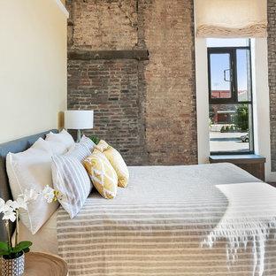 Foto de dormitorio tipo loft, urbano, sin chimenea, con paredes amarillas y suelo de madera en tonos medios