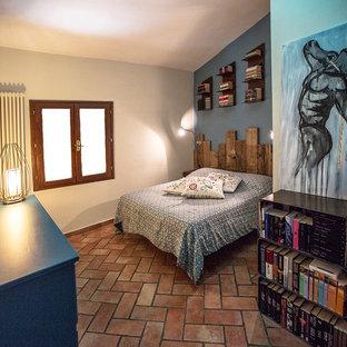 Foto de dormitorio principal, contemporáneo, pequeño, con paredes azules y suelo de baldosas de terracota