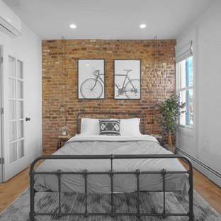 Urban medium tone wood floor bedroom photo in New York with white walls and no fireplace