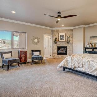 Imagen de dormitorio principal, clásico renovado, de tamaño medio, con paredes beige, moqueta, chimenea de esquina y marco de chimenea de piedra