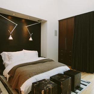 Imagen de dormitorio tipo loft, contemporáneo, con paredes negras y suelo de madera clara
