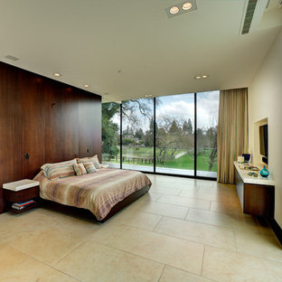 Inspiration for a large modern master bedroom in San Francisco with white walls, limestone floors, no fireplace and beige floor.