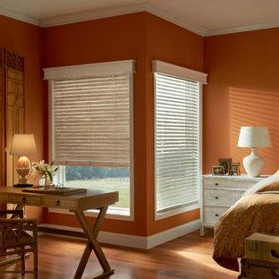 Imagen de dormitorio principal, tradicional renovado, grande, sin chimenea, con parades naranjas, suelo de madera en tonos medios y suelo marrón