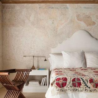 Aménagement d'une grande chambre méditerranéenne avec un mur beige et un sol en bois clair.
