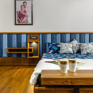 На фото: спальня в восточном стиле с белыми стенами, паркетным полом среднего тона и коричневым полом с