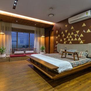На фото: спальня в восточном стиле с коричневыми стенами, темным паркетным полом и коричневым полом
