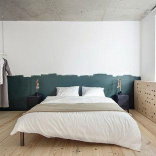 Exempel på ett litet industriellt huvudsovrum, med vita väggar och ljust trägolv