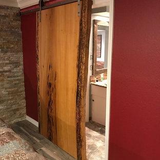 Imagen de dormitorio principal, rural, de tamaño medio, con paredes rojas, suelo de pizarra y suelo gris