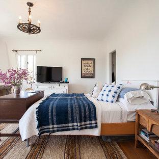 Idées déco pour une chambre parentale méditerranéenne avec un mur blanc, un sol en bois foncé, une cheminée d'angle et un manteau de cheminée en pierre.