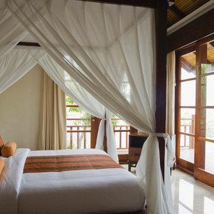 Diseño de dormitorio tipo loft, exótico, de tamaño medio, con paredes beige y suelo de baldosas de porcelana
