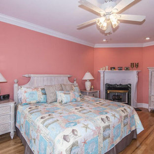 Large nautical master bedroom in Orlando with pink walls, medium hardwood flooring, a corner fireplace, a stone fireplace surround and brown floors.