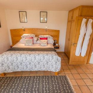 Foto de dormitorio principal, tradicional, de tamaño medio, con paredes blancas y suelo de baldosas de terracota