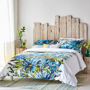 Immagine di una camera da letto tropicale con pareti bianche, pavimento in legno verniciato e pavimento bianco