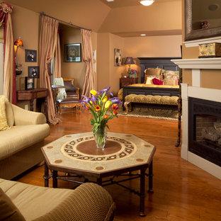 Modelo de dormitorio principal, de estilo americano, extra grande, con paredes beige, suelo de madera clara, chimenea de esquina y marco de chimenea de madera