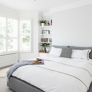 Scandinavian bedroom in London with white walls and carpet.