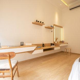 Imagen de habitación de invitados minimalista, de tamaño medio, sin chimenea, con paredes blancas, suelo de madera clara, marco de chimenea de yeso y suelo marrón