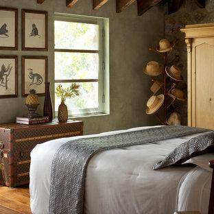 Foto de dormitorio rural con paredes grises, suelo de madera en tonos medios y suelo marrón