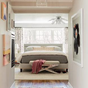 Immagine di una grande camera matrimoniale classica con pareti grigie, pavimento in legno massello medio, camino bifacciale, cornice del camino in intonaco e pavimento marrone