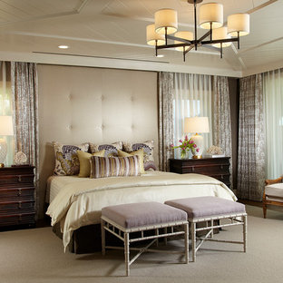 This is an example of a large tropical master bedroom in Tampa with brown walls and light hardwood floors.