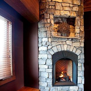Ispirazione per una camera degli ospiti rustica con pareti rosse, moquette, camino ad angolo e cornice del camino in pietra