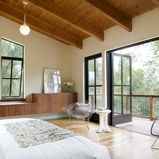 Example of a large trendy master light wood floor bedroom design in San Francisco with beige walls and no fireplace
