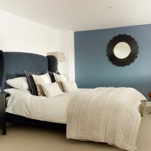 Immagine di una piccola camera matrimoniale classica con pareti blu e moquette