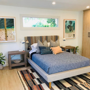 Inspiration for a mid-sized beach style loft-style bedroom in Other with white walls, porcelain floors and beige floor.