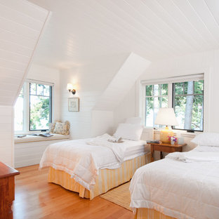 Coastal guest medium tone wood floor bedroom photo in Vancouver with white walls