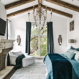 Mediterranes Hauptschlafzimmer mit weißer Wandfarbe, dunklem Holzboden und Kamin in Austin