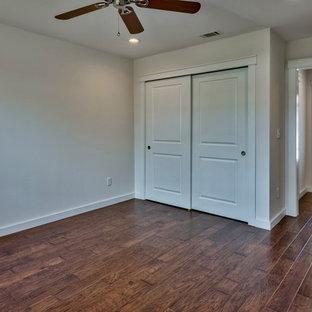 Klassisches Gästezimmer mit grauer Wandfarbe, braunem Holzboden und grünem Boden in Sonstige