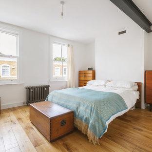 Идея дизайна: хозяйская спальня среднего размера в современном стиле с белыми стенами, паркетным полом среднего тона, фасадом камина из штукатурки и коричневым полом без камина