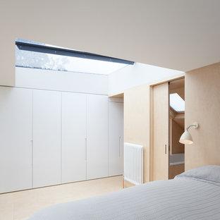 Ispirazione per una piccola camera matrimoniale design con pareti bianche, pavimento in compensato e nessun camino