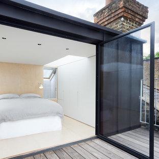 Cette photo montre une chambre parentale tendance avec un mur blanc et un sol en contreplaqué.