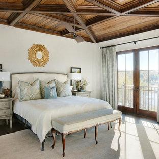 Modelo de dormitorio principal, costero, con paredes blancas, suelo de madera oscura y suelo marrón