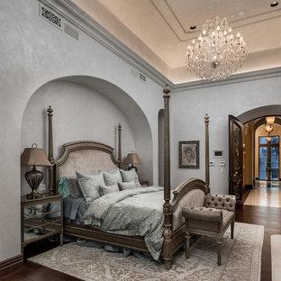 Geräumiges Mediterranes Hauptschlafzimmer mit grauer Wandfarbe, Kamin, braunem Boden, Porzellan-Bodenfliesen, Kaminumrandung aus Stein und eingelassener Decke in Phoenix