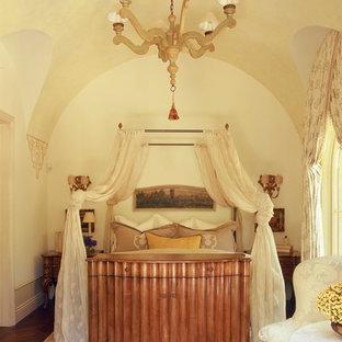 Foto på ett sovrum, med beige väggar och mörkt trägolv