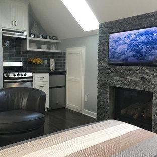 Imagen de dormitorio tradicional renovado, pequeño, con paredes grises, suelo de madera oscura, chimenea tradicional, marco de chimenea de piedra y suelo negro