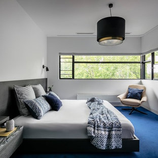 This is an example of a contemporary bedroom in Melbourne with white walls, carpet and blue floor.