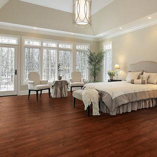 Imagen de dormitorio principal, tradicional renovado, de tamaño medio, con paredes beige, suelo de madera en tonos medios, chimenea tradicional y marco de chimenea de hormigón
