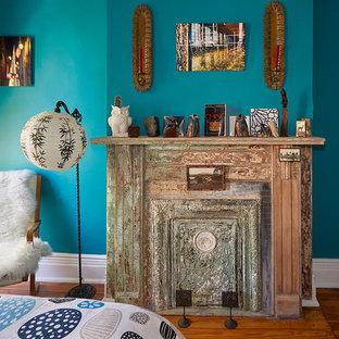 Mittelgroßes Eklektisches Hauptschlafzimmer mit blauer Wandfarbe, braunem Holzboden, Hängekamin und Kaminumrandung aus Metall in New York