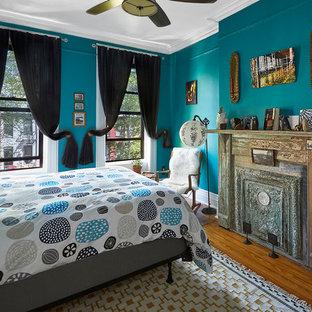 Foto di una camera matrimoniale eclettica di medie dimensioni con pareti blu, pavimento in legno massello medio, camino sospeso e cornice del camino in metallo