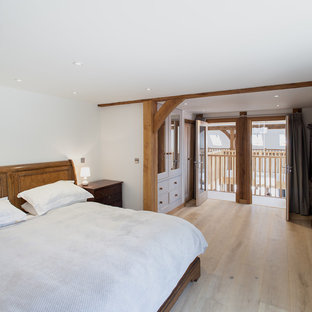Design ideas for a mid-sized arts and crafts master bedroom in Sussex with white walls, ceramic floors and beige floor.