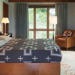 Ejemplo de dormitorio rural con paredes grises y suelo de madera en tonos medios