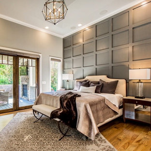 Inspiration for a large transitional master light wood floor and brown floor bedroom remodel in New York with gray walls, a standard fireplace and a stone fireplace