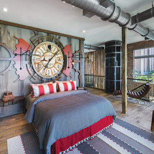 Design ideas for an industrial loft-style bedroom in Miami with multi-coloured walls and light hardwood floors.