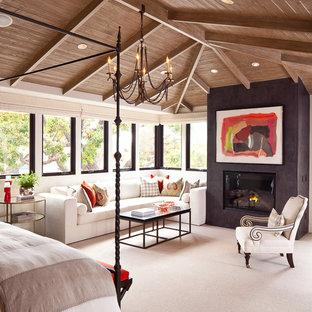 Неиссякаемый источник вдохновения для домашнего уюта: большая хозяйская спальня в средиземноморском стиле с ковровым покрытием, фасадом камина из штукатурки, белыми стенами и стандартным камином