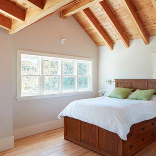 Diseño de dormitorio clásico renovado con paredes grises, suelo de madera en tonos medios y suelo marrón